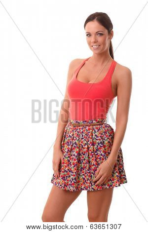 Summer photo of pretty young woman in mini skirt and top, smiling, looking at camera.