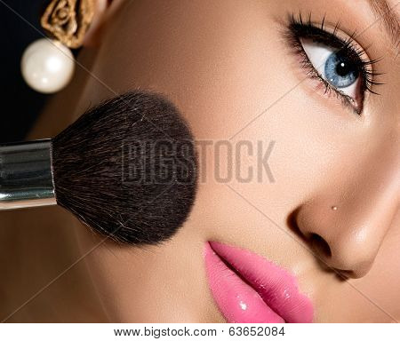 Makeup. Make-up Applying closeup. Cosmetic Powder Brush for Make up. Beauty Girl with Perfect Skin. Blue eyes, Pink Lipstick. Isolated on Black Background. Makeover