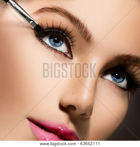 Makeup. Make-up Applying closeup. Eyeliner. Cosmetic Eyeshadows. Eyeline brush for Make up. Beauty Girl with Perfect Skin. Eyelashes. Blue eyes, Pink Lipstick. Isolated on Black Background. Makeover