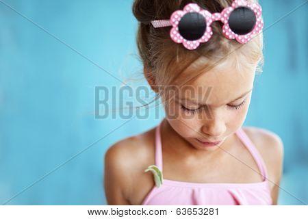 7 years old child holding seashell on blue background