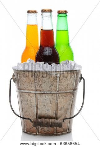 An old fashioned bucket filled with ice and soda bottles. Three different pop bottles are represented, orange, cola and lemon lime. Vertical format on a white background with reflection.
