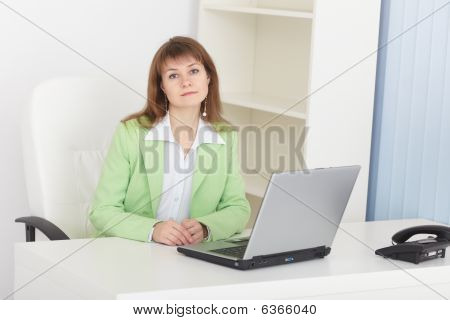 Businesswoman Sits At Table At Light Office With Laptop