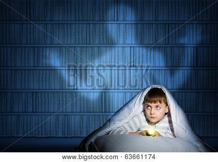 boy under the covers with a flashlight
