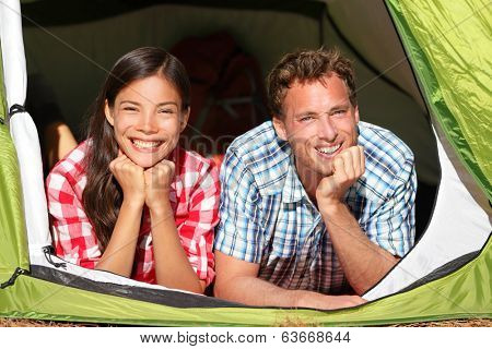 Happy romantic couple camping in tent looking in forest. Campers smiling happy outdoors in forest relaxing. Multiracial couple having fun relaxing after outdoor activity. Asian woman, Caucasian man.