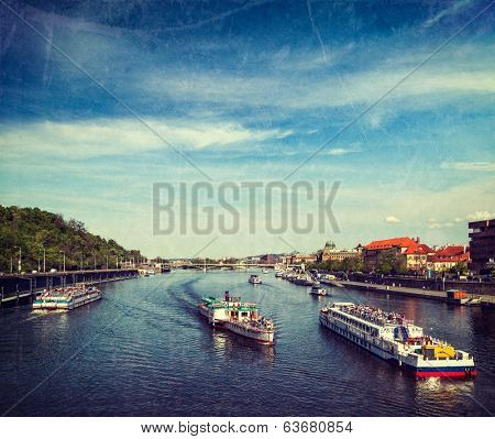 Vintage retro hipster style travel image of turist boats on Vltava river in Prague, Czech Republic with grunge texture overlaid