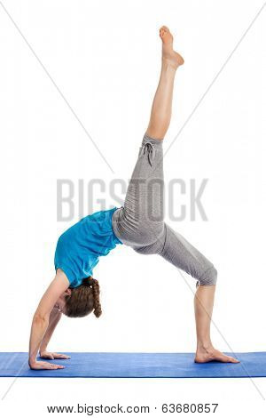 Yoga - young beautiful slender woman yoga instructor doing One-legged Upward Bow Pose (ekapada urdhva dhanurasana) asana exercise isolated on white background