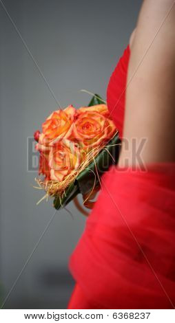 Bride, wearing  silk red gown, holding beautiful bouquet of the roses