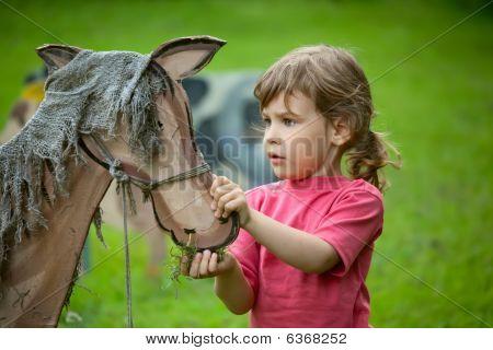 La niña alimenta un caballo de madera