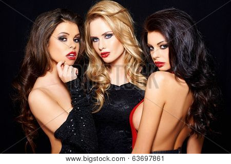Three beautiful enticing glamorous woman posing together on a dark background looking seductively at the camera with sultry thoughtful expressions
