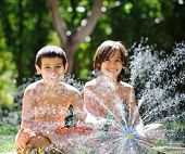 image of sprinkler  - Happy kids playing and splashing with water sprinkler on summer grass yard - JPG