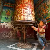 KATHMANDU, NEPAL - DEC 23, 2013: Unidentified children have fun with spinning Big Tibetan Buddhist p