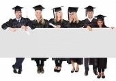 stock photo of white gown  - Group of graduate students presenting empty banner - JPG