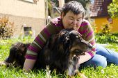 stock photo of disable  - mentally disabled woman is lying with dog on a lawn - JPG
