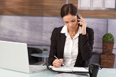 Businesswoman sitting at desk in office, talking on mobilephone, writing notes to organizer, having