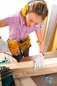 image of hand drill  - Female carpenter at work using hand drilling machine - JPG