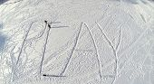 Aerial view to three children drawing big word PLAY on the snow in winter