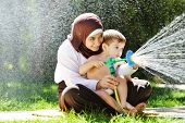 stock photo of fountain grass  - Beautiful Middle Eastern Arabic girl having baby playing with water sprinkler in garden - JPG