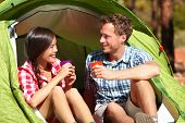 Camping couple drinking water in tent smiling happy outdoors in forest enjoying sun at looking at vi