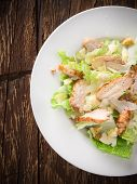 pic of caesar salad  - Caesar salad with chicken and greens on wooden table - JPG