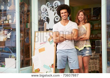 Owners Of Delicatessen Standing Outside Shop Together
