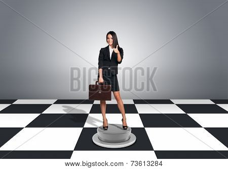 Beautiful businesswoman holding briefcase and showing thumb-up