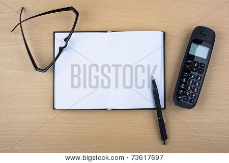 Open notebook and black phone on wooden texture.