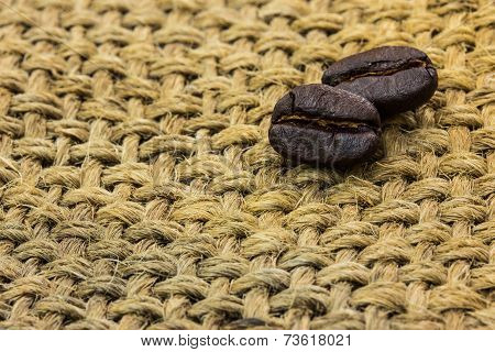 Coffee beans on a sacking background .