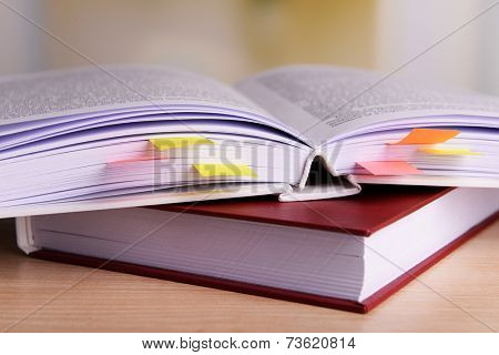 Books with bookmarks on table on bright background