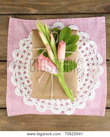 Natural style handcrafted gift box with fresh flowers and rustic twine, on wooden background