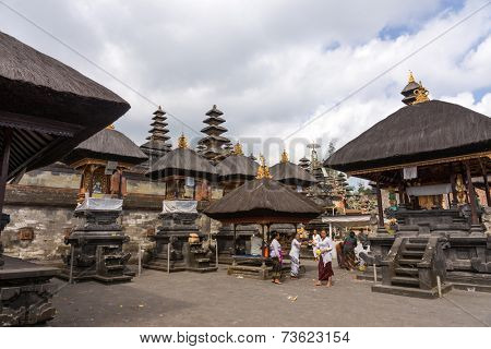 BALI, INDONESIA - SEPTEMBER 20, 2014: Hindu devotees from a family perform the Nyaben 11th day ceremony at the Besakih Temple Complex. This is the largest and most important Hindu temple in Bali.