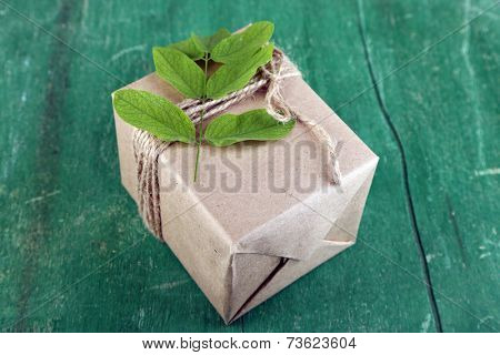 Natural style handcrafted gift box with fresh leaves and rustic twine, on wooden background