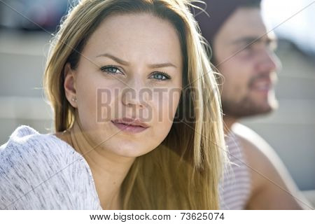 Pretty young woman looking into the camera with her boyfriend out of focus in the background