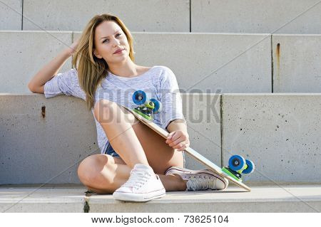 Young woman, sitting comfortably on concrete steps, holding her skateboard on a warm, sunny afternoon