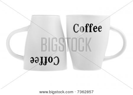 Two white coffee cups one upside-down isolated on white