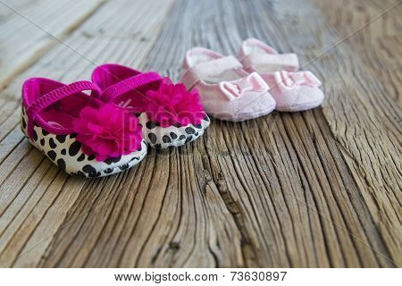 Sweet Fancy And Colorful Baby Shoes On The Wooden Table