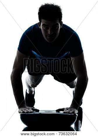 one  man exercising push ups on bosu workout fitness in silhouette studio isolated on white background