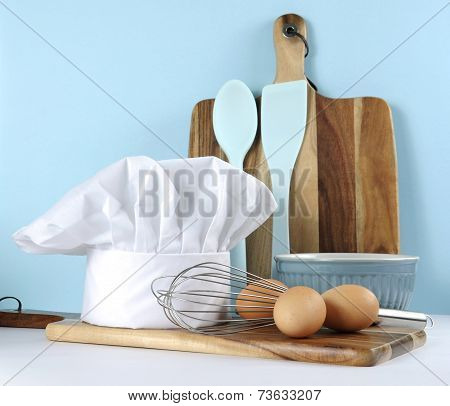 Modern Kitchen Cooking Kitchenware And Chef's Hat With Mixing Bowl, Whisk, Chopping Boards And Eggs