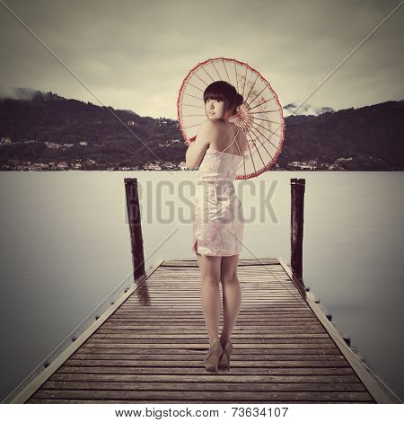 Young Pretty Chinese Girl Dressed In Traditional Pink National Dress Posing On Old Wooden Pier
