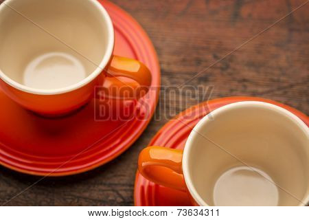two empty stoneware coffee cups against grunge wood table, shallow depth of field