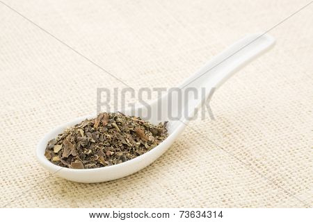 bladder wrack seaweed leaves on a white Chinese spoon against burlap canvas