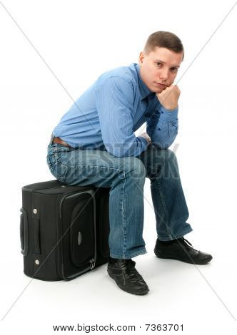 Pensive Young Man Sitting On A Hand Bag