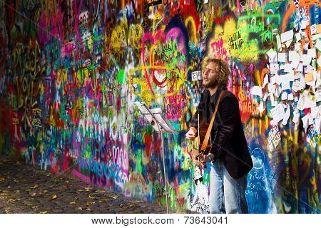 Street Busker Performing In Front Of John Lennon Graffiti Wall
