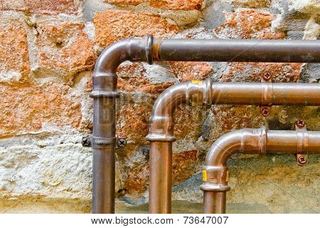 Three Curving Pipes On A Brick Wall