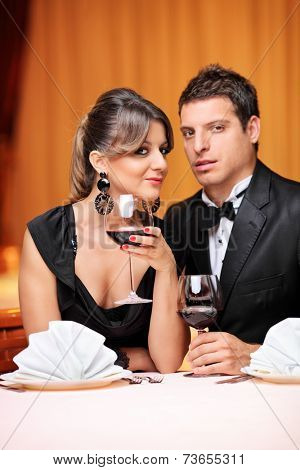 Vertical shot of a classy couple sitting at a table in a restaurant