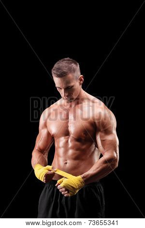 Vertical shot of a handsome boxer bandaging his hands on black background