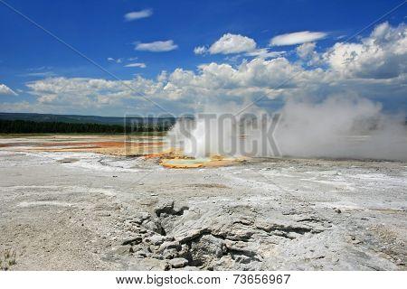Geyser Basin Erupts Against Blue Sky