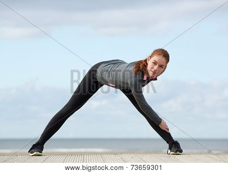 Sportswoman Stretching Leg Muscles Outdoors