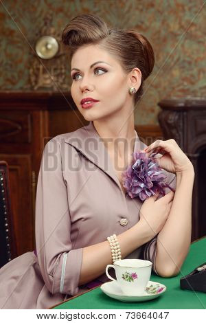beautiful young woman drinking tea in vintage interior