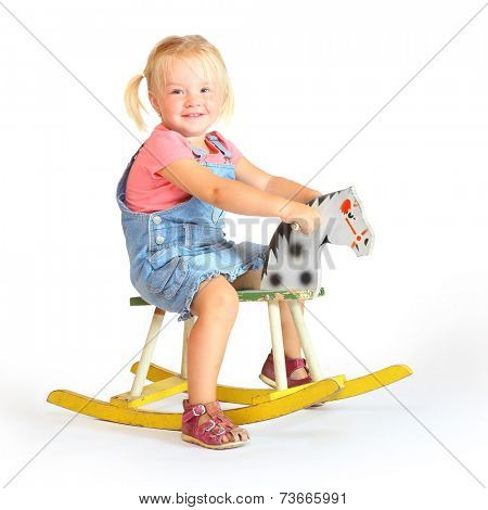 Happy girl on a rocking horse.