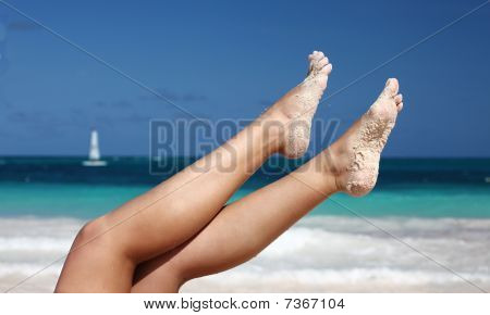 Woman`s Legs On Tropical Beach Background
